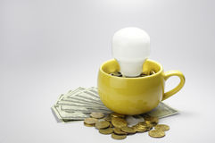 Lightbulb and Cup full with money - Finance Concept Royalty Free Stock Photo