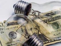 A lightbulb on dollar bill. Energy saving concept royalty free stock photography