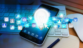 Lightbulb en pictogrammen over mobiele telefoon Royalty-vrije Stock Afbeelding
