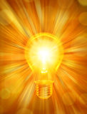Lightbulb Energy Background. A light bulb on a warm glowing background with rays of light Royalty Free Stock Images