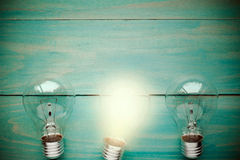 Lightbulb glowing among the others. Glow among other lightbulb on a wooden background Stock Photo