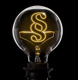 Lightbulb with a glowing wire in the shape of a paragraph symbol Stock Image