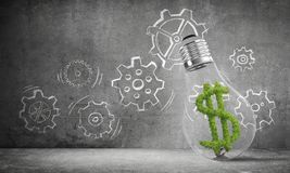 Concept of effective business innovations. Lightbulb with green dollar symbol ine placed against sketched gear mechanism on wall on background. 3D rendering Stock Photo