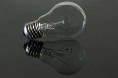 Lightbulb on grey background. Lightbulb on grey reflecting background Royalty Free Stock Photo