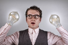 Lightbulb Hands. Nerdy four eyed businessman is shocked by his lightbulb hands Royalty Free Stock Photography