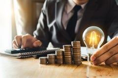 Lightbulb med att använda bunten för bärbar datordator och pengar arkivfoto