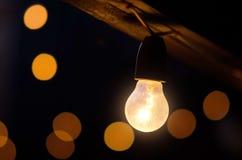 Lightbulb at night outside Stock Images