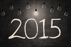 Lightbulb and number of 2015. Bright light bulb illuminate the number 2015 on blackboard Stock Image