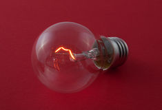 Lightbulb op een rode oppervlakte Stock Fotografie