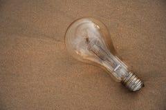 Lightbulb på sand Arkivbilder