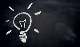 Lightbulb painted with chalk on blackboard concept.  royalty free stock images