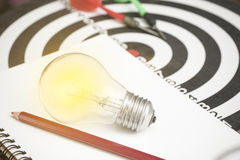 Lightbulb on paper book and dartboard with arrow. Concept for new ideas with innovation and creativity Stock Photo