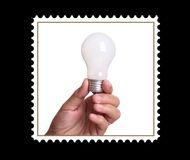 Lightbulb in a postage stamp. Lightbulb in a hand isolated on black  background Stock Photos
