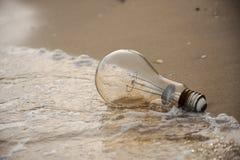 Lightbulb on sand Stock Images