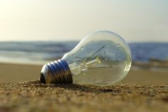 The lightbulb is saved after almost drownd and the sun begun to shine over it stock photos