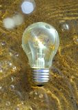 Lightbulb som svävar i vattnet som är vid liv med lite av ljus royaltyfri bild