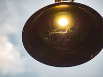 Lightbulb and spiderweb. On sky Royalty Free Stock Images