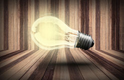 Lightbulb  on wood planks texture background Stock Images