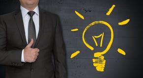 Lightbulbconcept en zakenman met omhoog duimen stock afbeelding