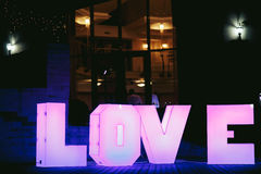 Lighted big pink letters LOVE before the restaurant Royalty Free Stock Photos