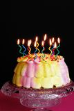 Lighted Birthday Cake. Lighted candles on a pink and yellow iced birthday cake on a decorative cake plate in front of a black background Royalty Free Stock Photography