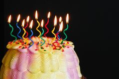 Lighted Birthday Cake. Burning candles on a pink and yellow iced birthday cake in front of a black background royalty free stock photos