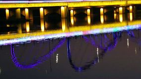 Lighted bridge reflection on river night view. Xingxvjiang bridge reflection on river night view in Nanning city China stock video