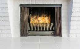 Lighted and burning fireplace in retro style but with a modern look background architecture is of white brick stones and white til stock photography