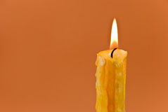 Lighted candle on the brown background Royalty Free Stock Images