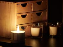 Lighted candle in a dark room, on the bed side royalty free stock image