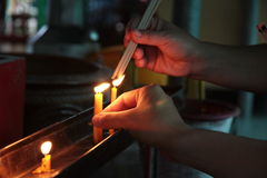Lighted candle and incense for Buddha. Selective focus. Royalty Free Stock Photography