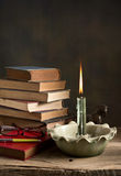 Lighted candle and old books Stock Photos