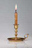 Lighted candle in an old brass candlestick. Stock Photo