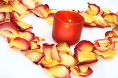 Lighted candle and petals. Lighted candle in red glass jar surrounded by red and yellow petals forming a heart shape Stock Photo