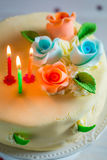 Lighted candles and birthday cake Royalty Free Stock Image