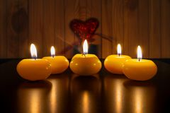 Lighted candles are on the black table on the wooden background with red heart which is on the green candlestick. Diwali festival