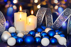 Lighted candles and blue white Christmas tree decorations on the Stock Photo