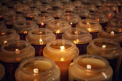 Lighted candles in catholic church. Rows of multiple lighted candles in catholic church royalty free stock image