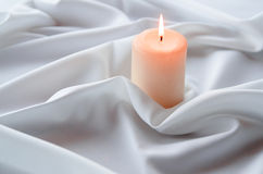 Lighted candles on a crumpled tablecloth. Lighted candles on a white crumpled tablecloth Stock Image