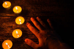 Lighted candles and hand on a wooden Royalty Free Stock Photography