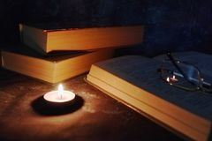 Lighted candles in an intimate setting, old books, yellowed from time to time, glasses in a knitted yellow thread royalty free stock photo