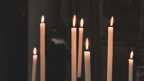 Lighted candles with statue of the madonna in the background stock photo