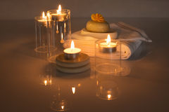 Lighted candles with towels and soap with a flower Stock Photos