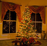 Lighted christmas tree in cozy home Stock Image