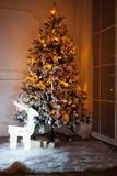 A lighted Christmas tree with presents underneath. In living room stock image