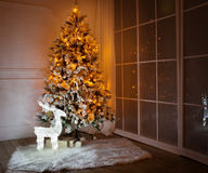 A lighted Christmas tree with presents underneath. In living room stock photos