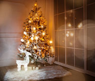 A lighted Christmas tree with presents underneath Royalty Free Stock Images