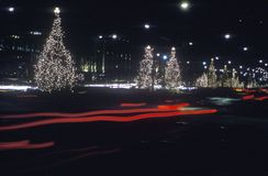 Lighted Christmas trees along roadside and automobile taillights at night, New York Stock Photos