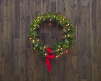Lighted Christmas wreath, on wood background with red ribbon stock image