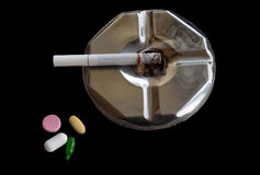 Lighted cigarette on an ashtray alongside medicine pills. Royalty Free Stock Image